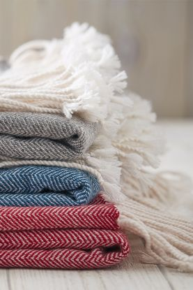 Cashmere and herringbone throw in grey, blue and red.